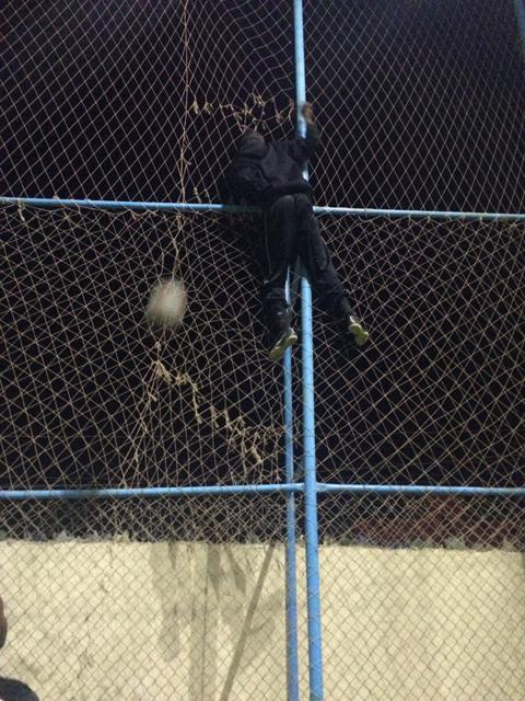 ネットをよじ登り挟まったボールを楽々取るソマリ人